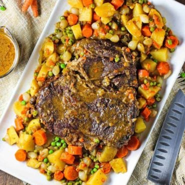 An overhead view of a classic pot roast on a large platter surrounded by potatoes, carrots, and peas.
