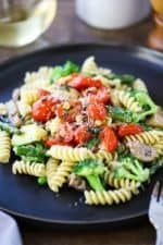 A dark dinner plate filled with a serving of pasta primavera with sautéed tomatoes on top.