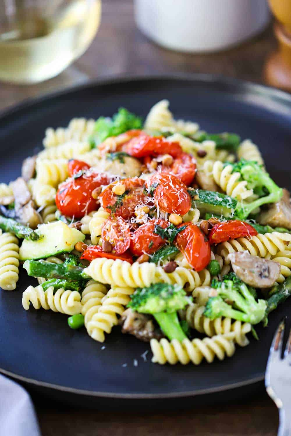 A dark dinner plate filled with a serving of pasta primavera with sauteed tomatoes on top.