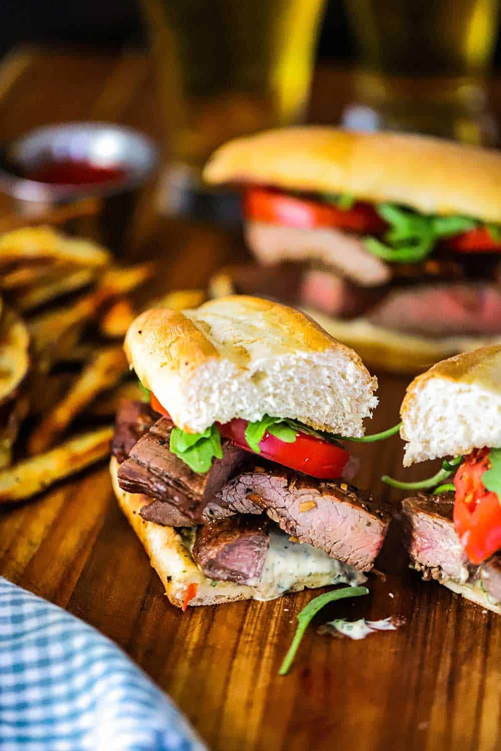 A grilled steak sandwich that has been cut in half and is sitting on a cutting board next to steak fries.