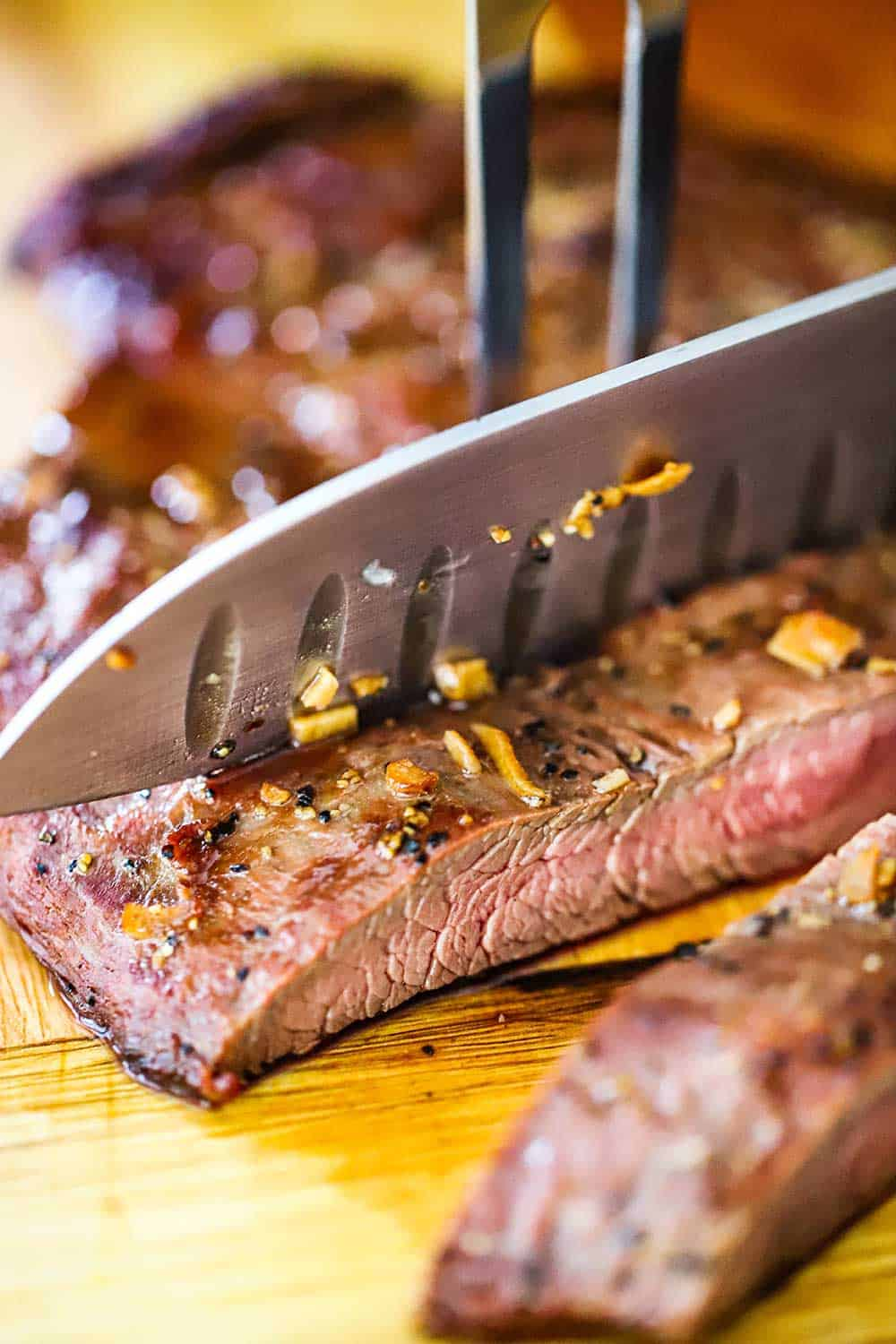 A large chef's knife cutting through a grilled flank steak with a large fork holding it in place.