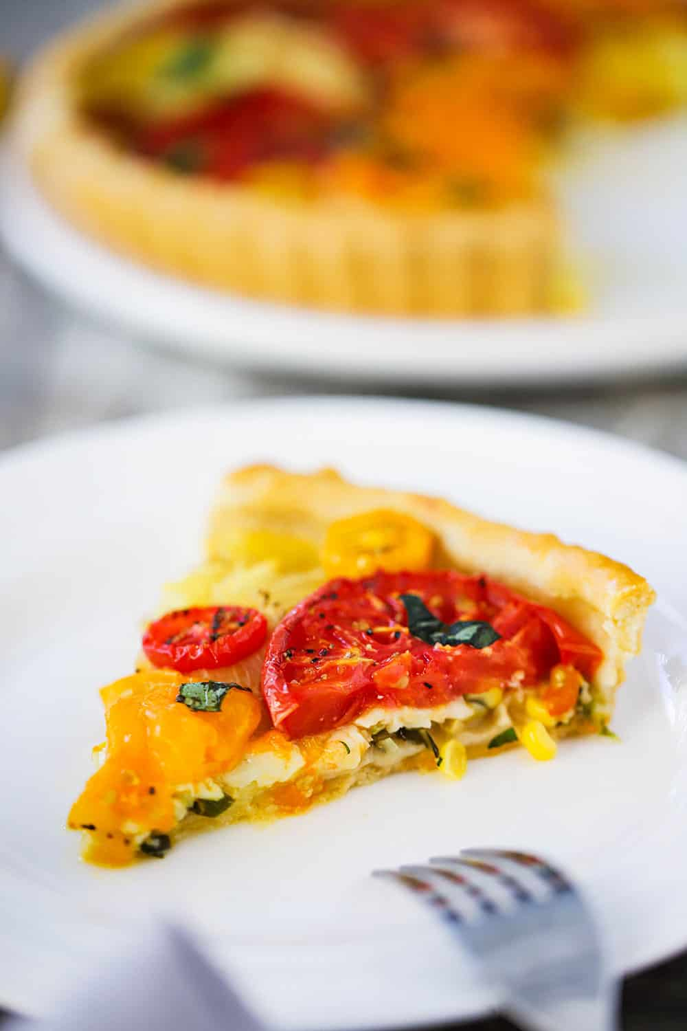 A slice of a tomato tart with corn and herbs on a small white plate next to a fork.