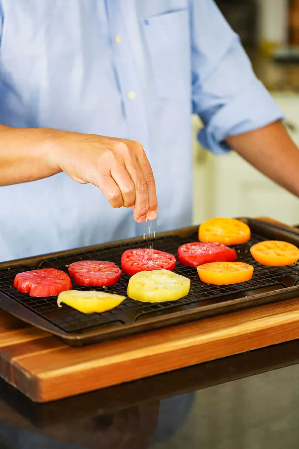 A person sprinkling salt onto sliced tomatoes on a baking rack in a baking sheet on a cutting board.