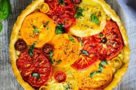 Looking straight down at a tomato tart with corn with fresh tomatoes nearby.
