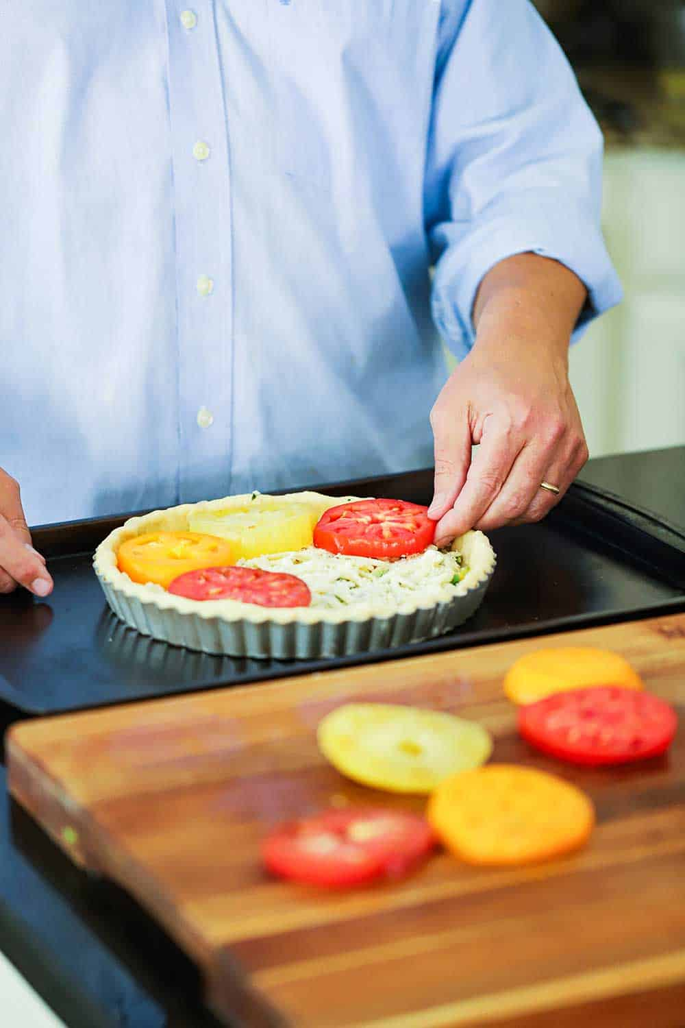 A person layering sliced heirloom tomatoes into a tart pan filled with cheese and corn.