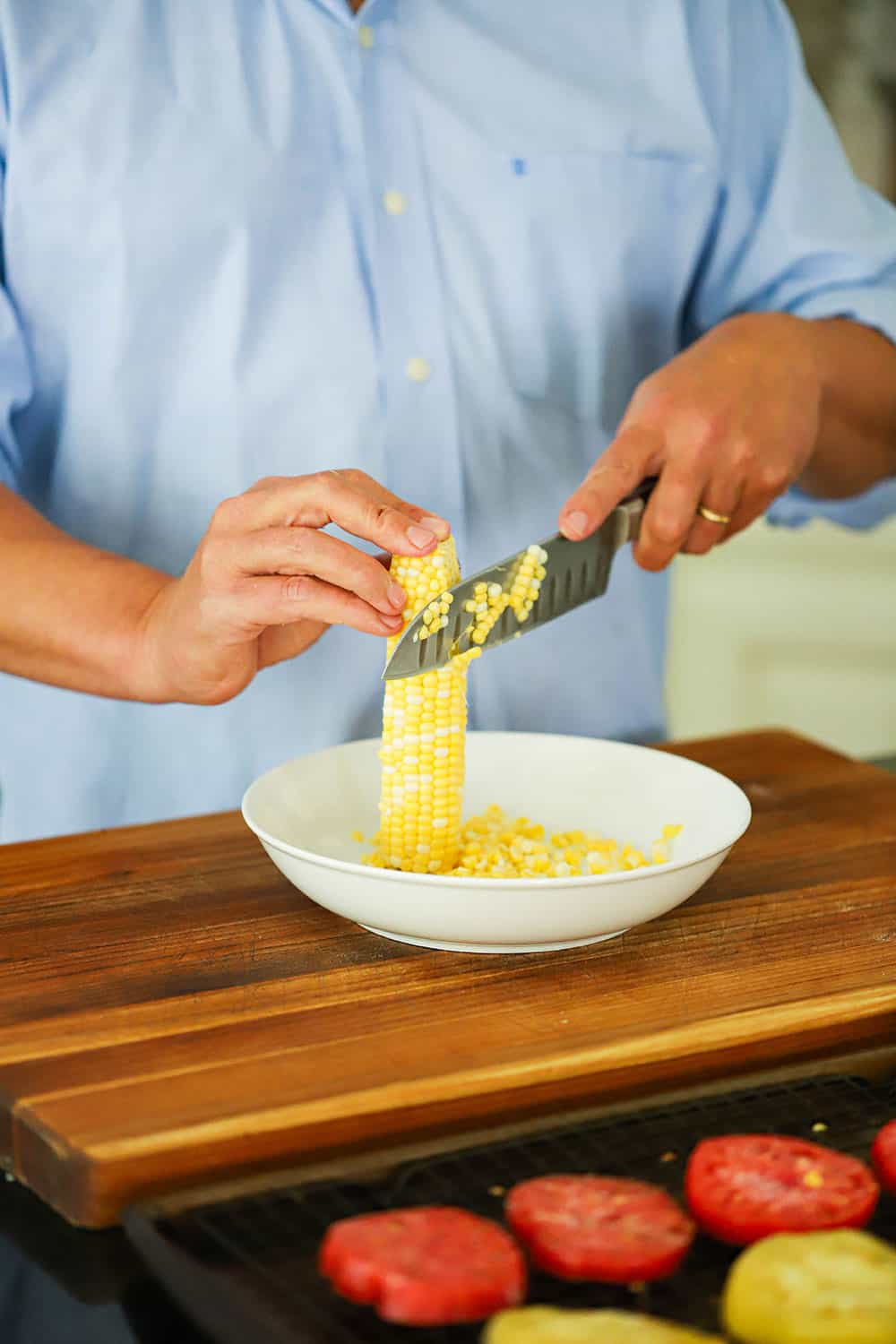 A person holding a ear of fresh corn upright in a bowl and using a knife to cut off the kernels.