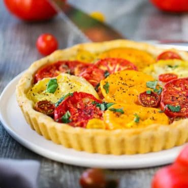 A tomato tart with colorful sliced tomatoes on top in a pastry shell all on a white serving plate.