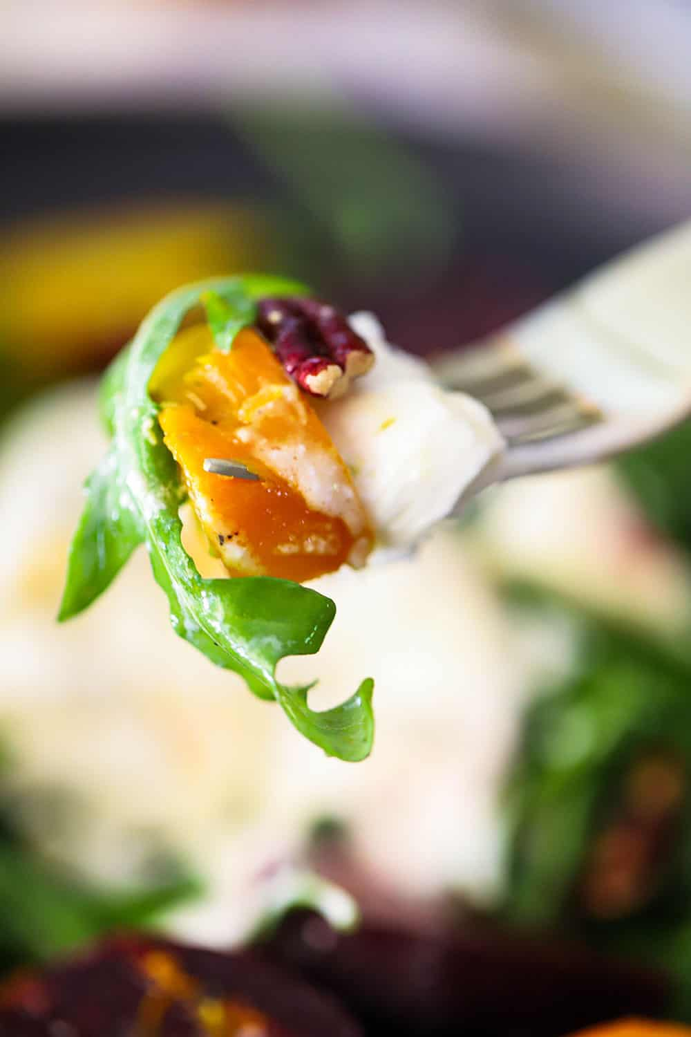A fork holding up a piece of burrata cheese, roasted golden beet, and arugula salad.