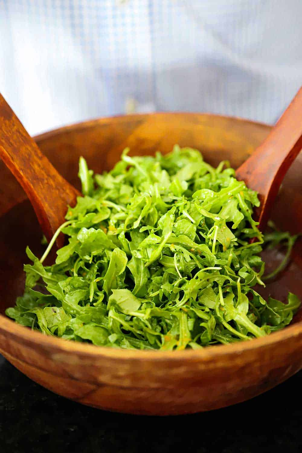 A large wooden salad bowl filled with baby arugula being tossed by a couple of wooden spoons.