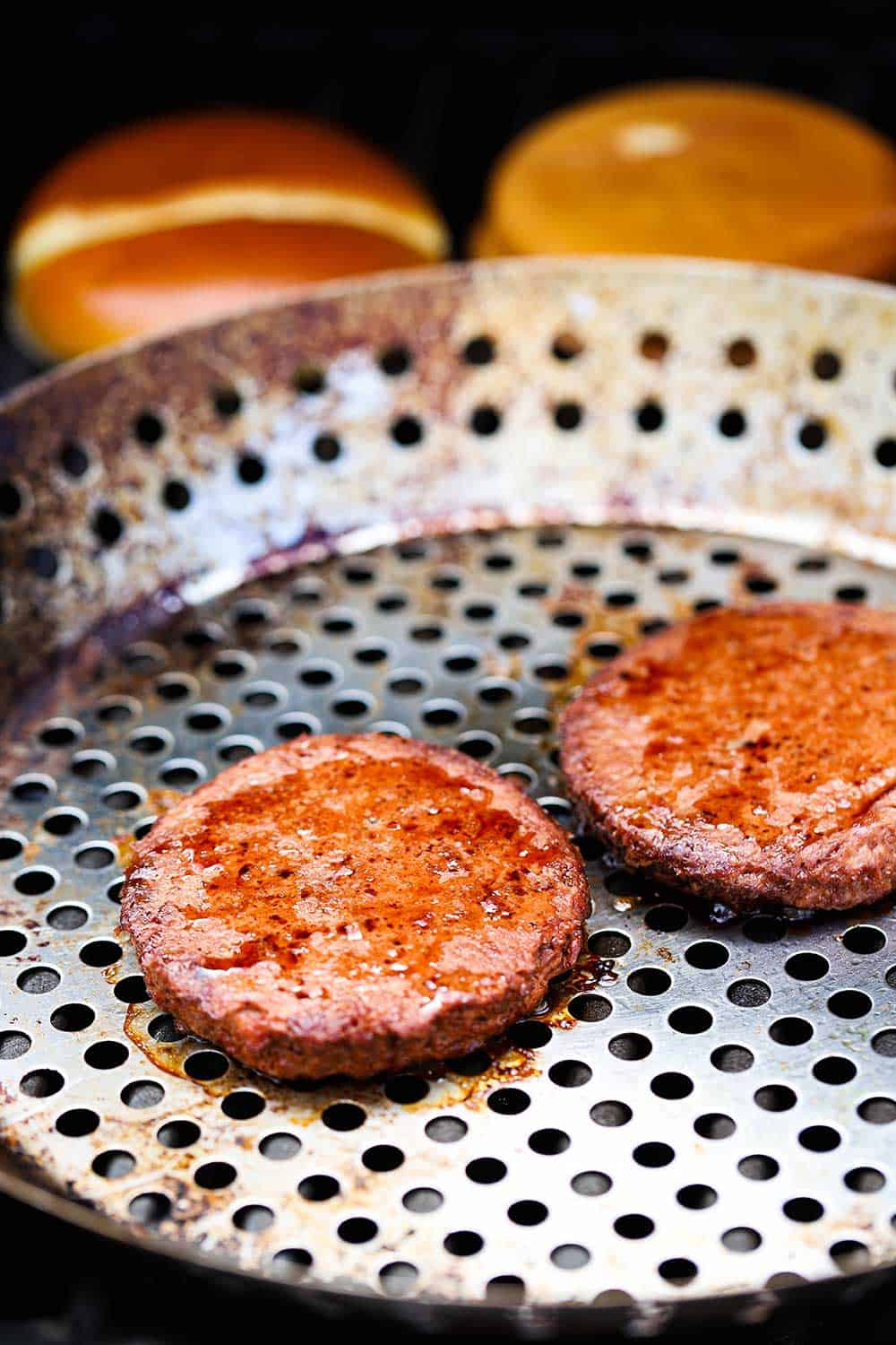 Two plant-based burgers on a grill pan on a grill in front of two hamburger buns, also on the grill.