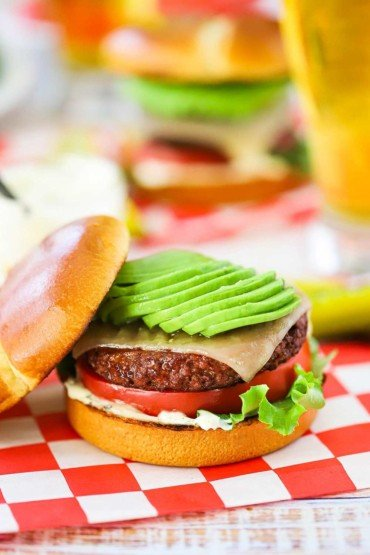 A plant-based California burger topped with sliced avocado sitting on a red-checkered napkin.