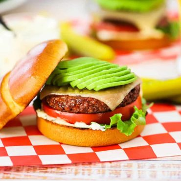 A plant-based California burger topped with sliced avocado sitting on a red-checkered napkin in front of an OZO package.