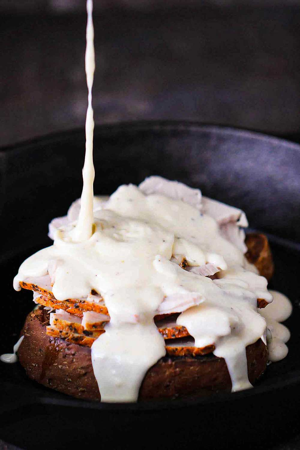 A cast iron skillet filled with a Kentucky hot brown with Mornay sauce being poured over the top.