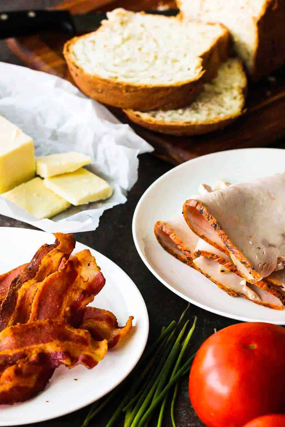 White plates filled with cooked bacon, slice turkey, butter, and surrounded by a tomato and sliced bread.