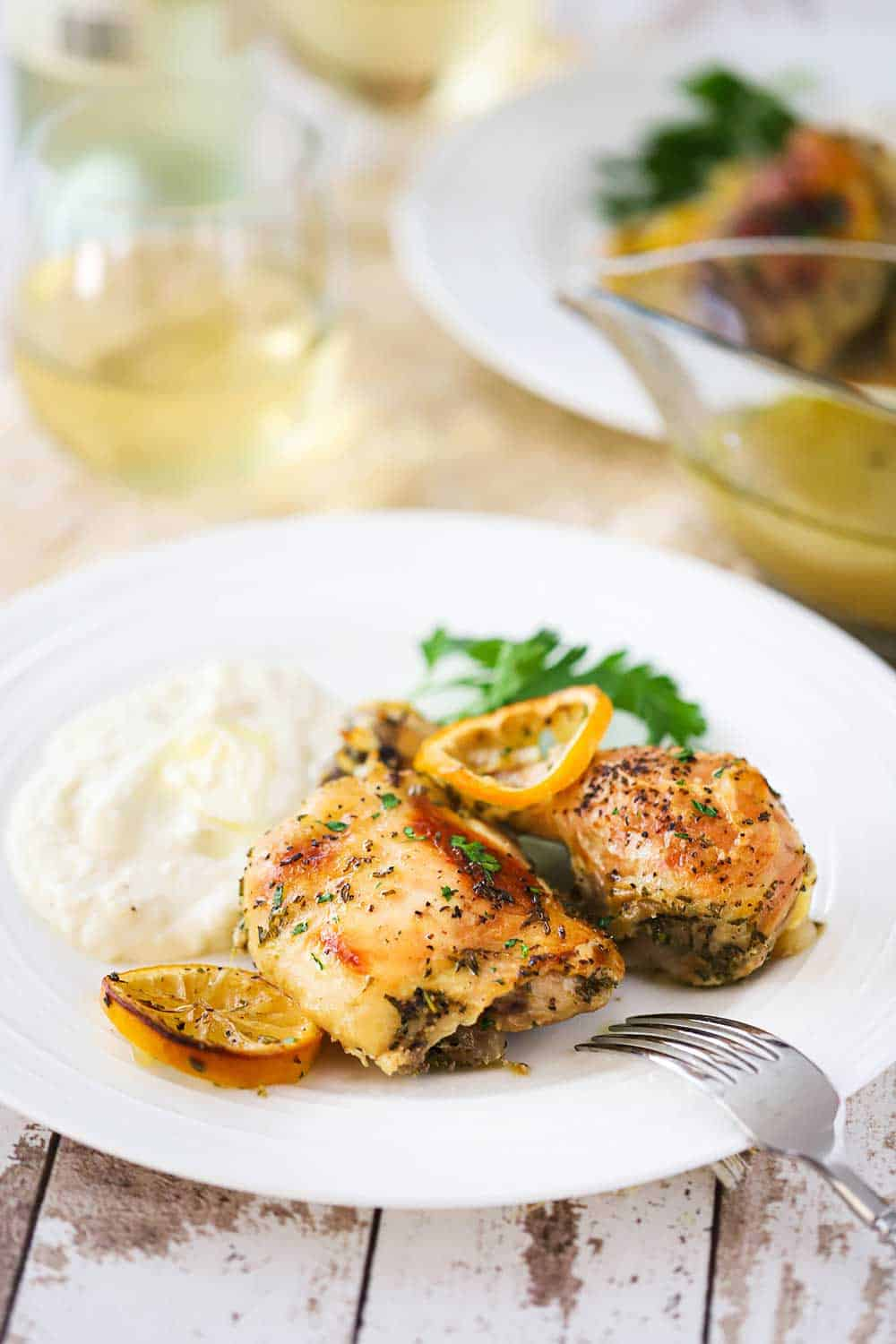 A white plate filled with two roasted chicken pieces, a lemon slice, and mashed potatoes next a glass of white wine.