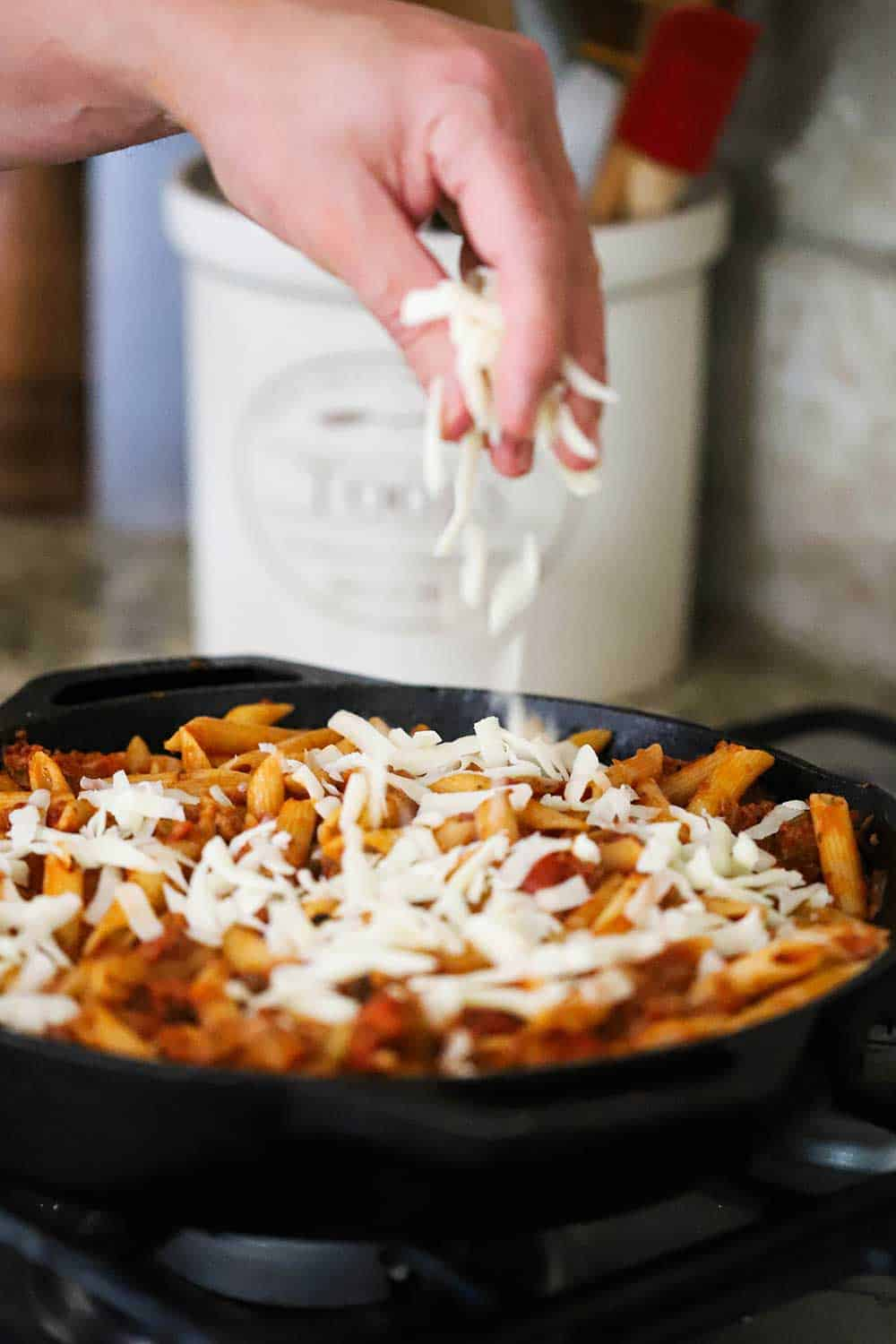 A hand sprinkling grated mozzarella cheese over a pan filled with pasta and sauce.