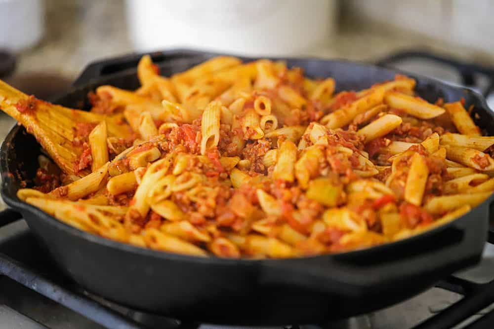 A cast-iron skillet filled with pasta in a vegetable sauce.