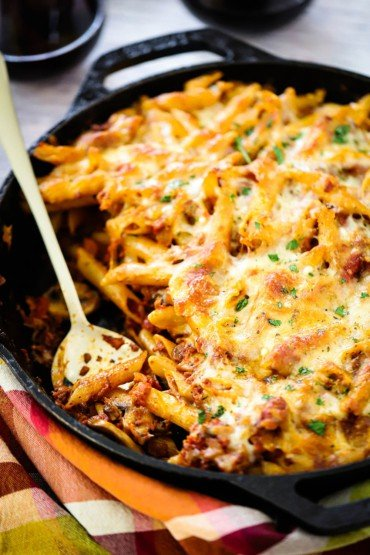A large cast-iron skillet filled with vegetarian pasta bake with a spoon in it.