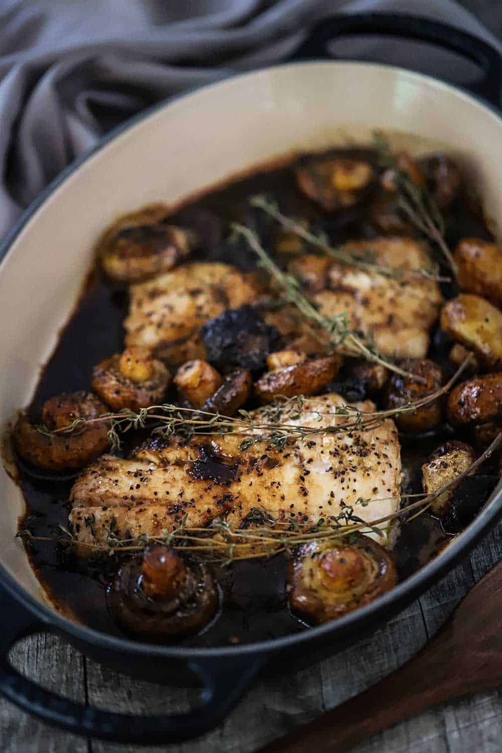 A baking dish filled with seared haddock with mushroom agrodolce sauce and sprigs of thyme on top.