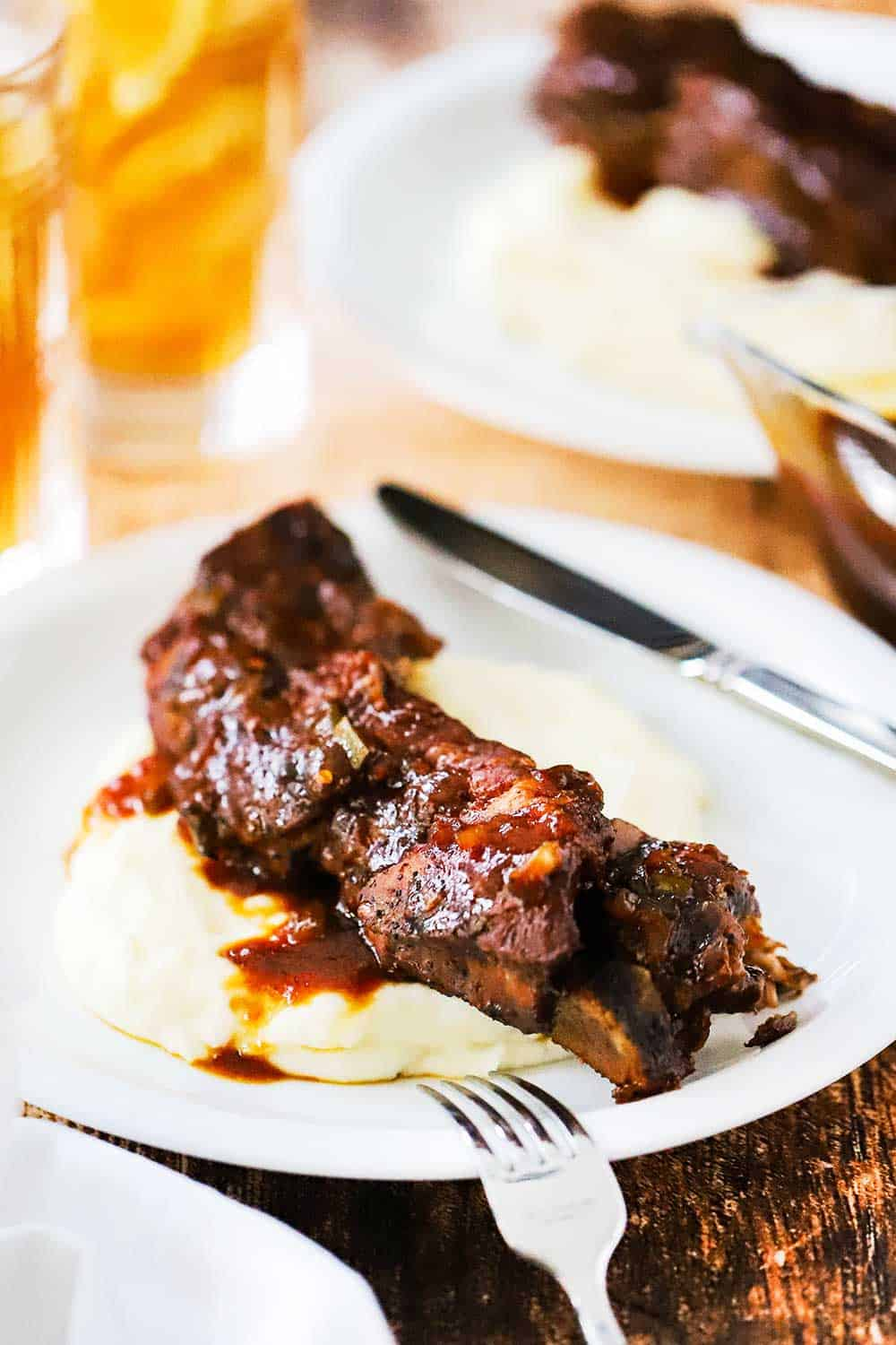 A white plate filled with a serving of mashed potatoes with a country-style ribs and sauce on top of it.