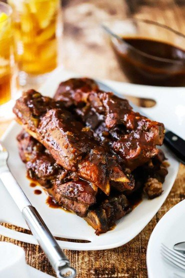 A white platter with a stack of country-style pork ribs next to two glasses of iced tea.