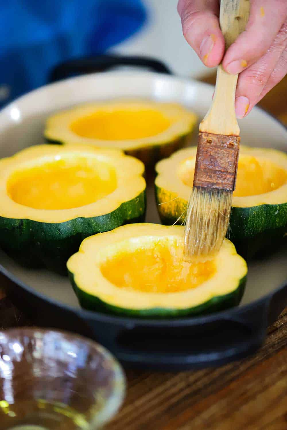 A hand brushing olive oil onto acorn squash that has been cut in half and sitting in a baking dish.