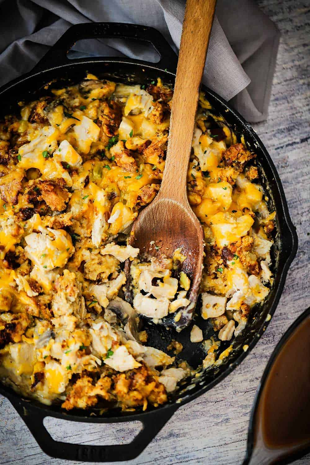 A large black cast-iron skillet filled with turkey and stuffing dressing with some of the food scooped out.