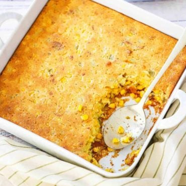 A square white baking dish filled with corn casserole next to a plate filled with the same.