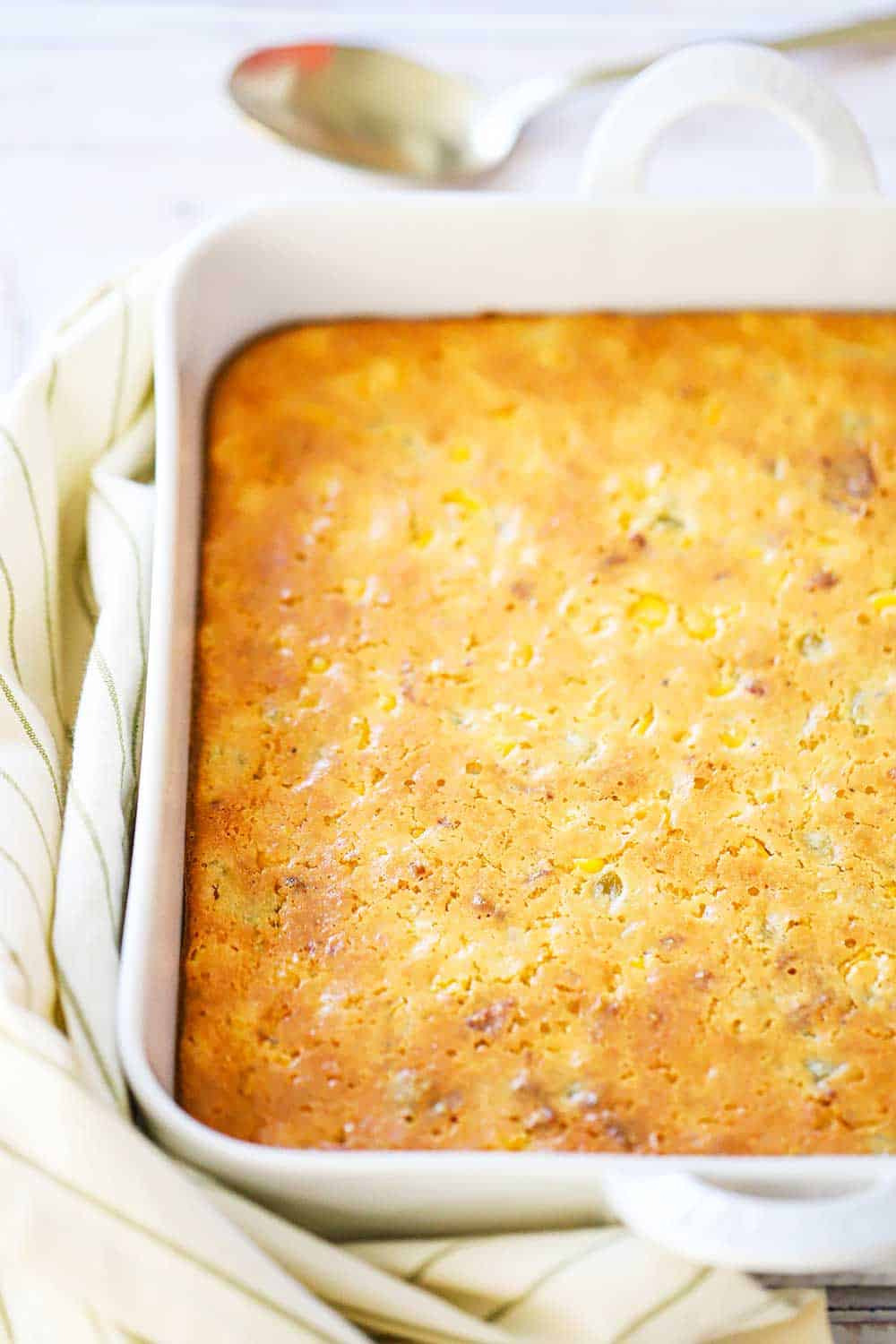 A fully cooked corn casserole in a square white baking dish next to a gold serving spoon.