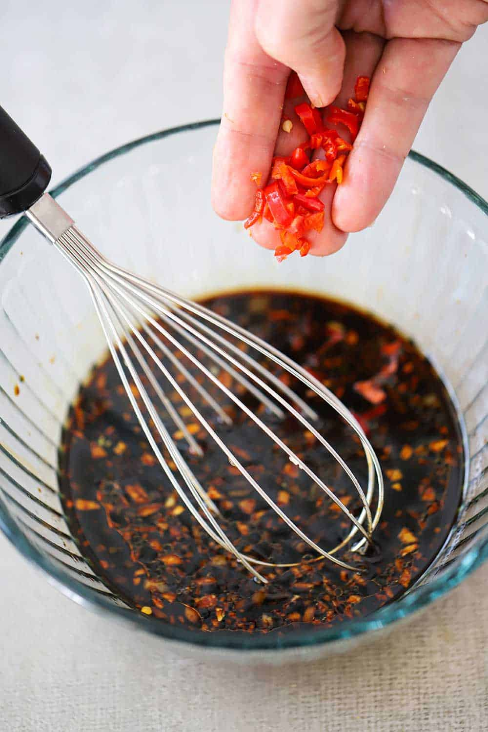 A hand dropping chopped red peppers into a glass bowl of ginger soy dipping sauce.