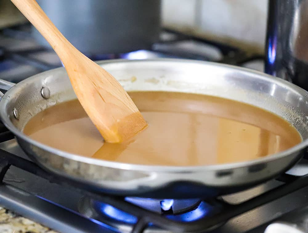 A large stainless steel skillet filled with brown gravy with a wooden spoon in it.