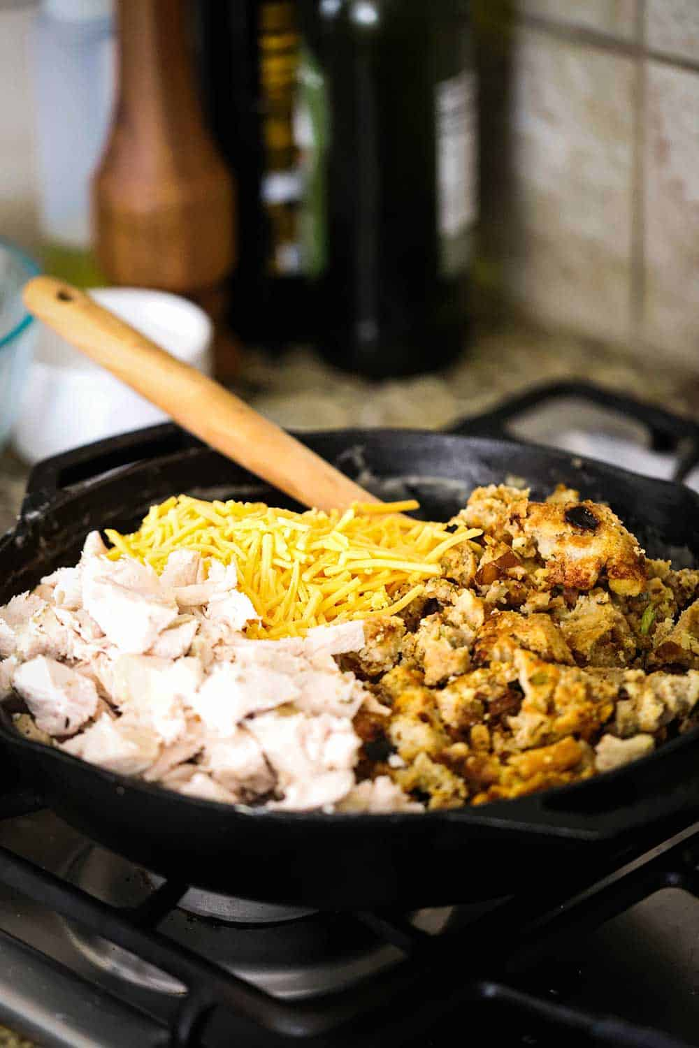 A large black cast-iron skillet filled with roast turkey pieces, broken up dressing, and shredded cheddar cheese, along with a wooden spoon.