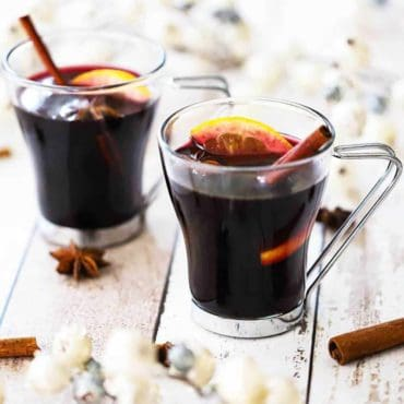 Two clear glasses filled with mulled wine and garnished with a cinnamon stick, star anise, and an orange slice.