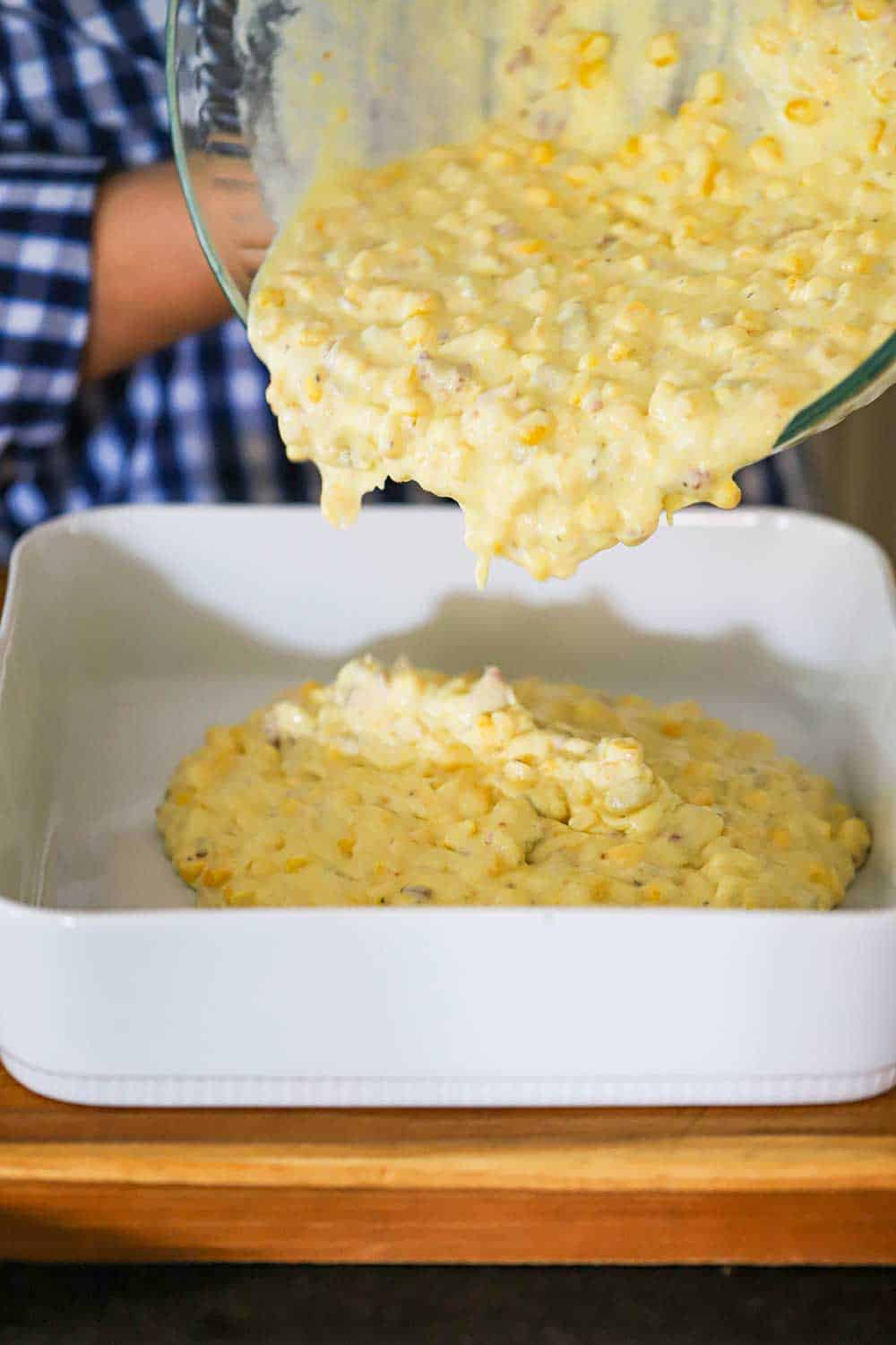 A person pouring a corn casserole uncooked mixture into a square baking dish.