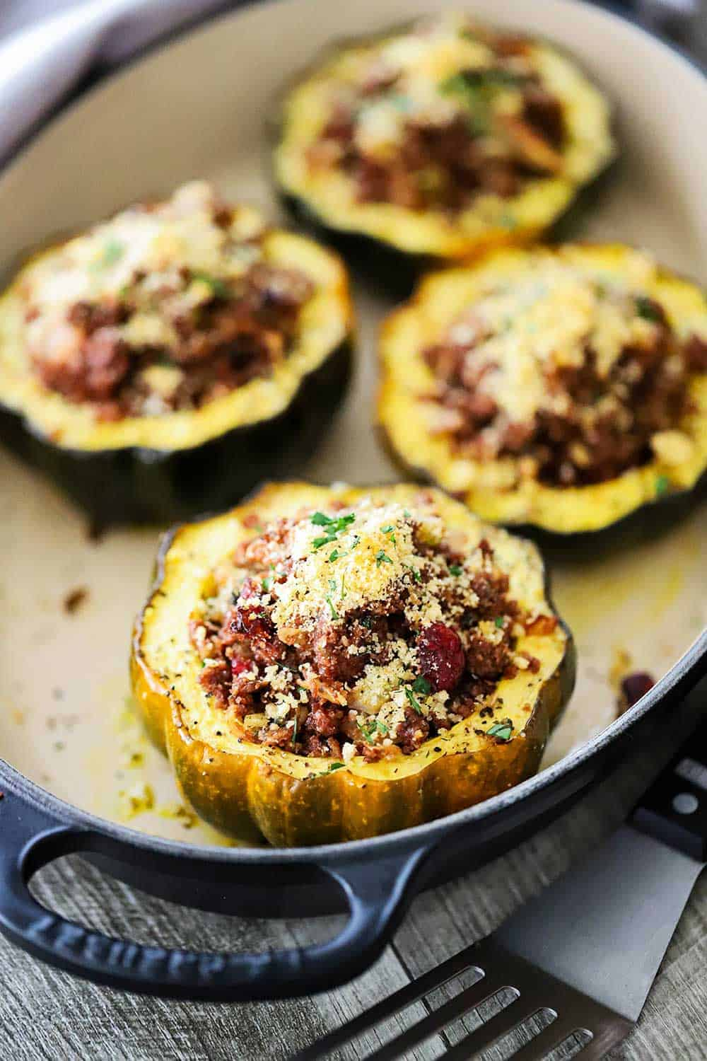 4 stuffed acorn squash filled with a vegetarian stuffing all in a oval baking dish.