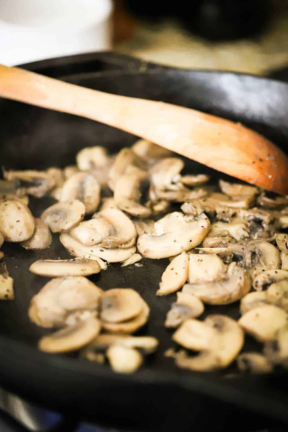 A black cast-iron skillet with sliced mushrooms being sautéd in it, with a wooden spoon in the pan, also.