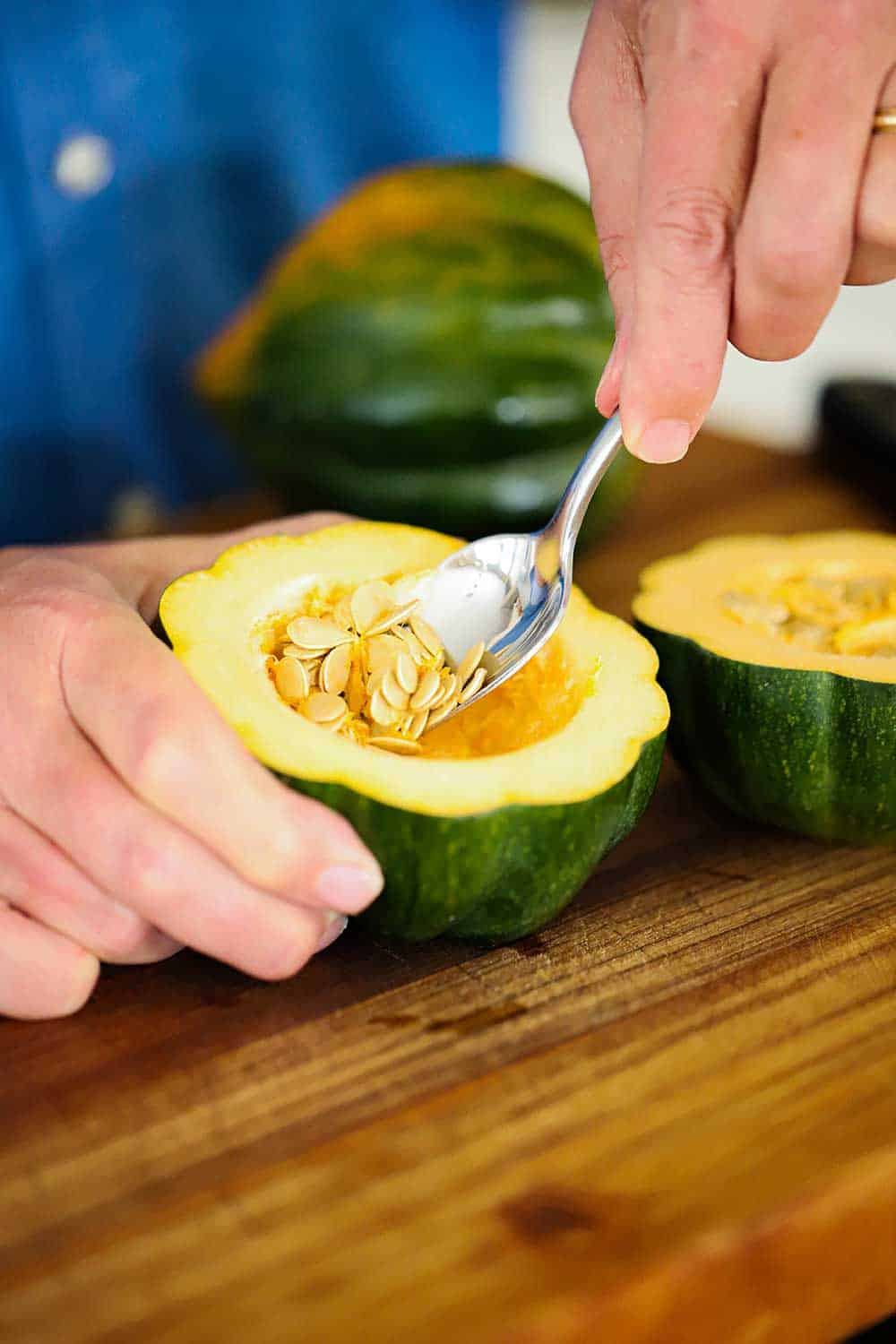 A person using a spoon to remove seeds from the center of an acorn squash that has been cut in half.