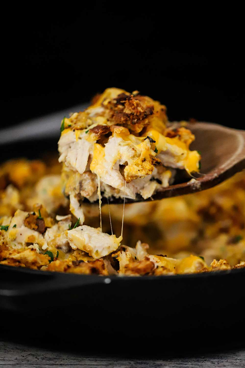 A large wooden spoon lifting gooey cheesy turkey and stuffing casserole from a cast-iron skillet.