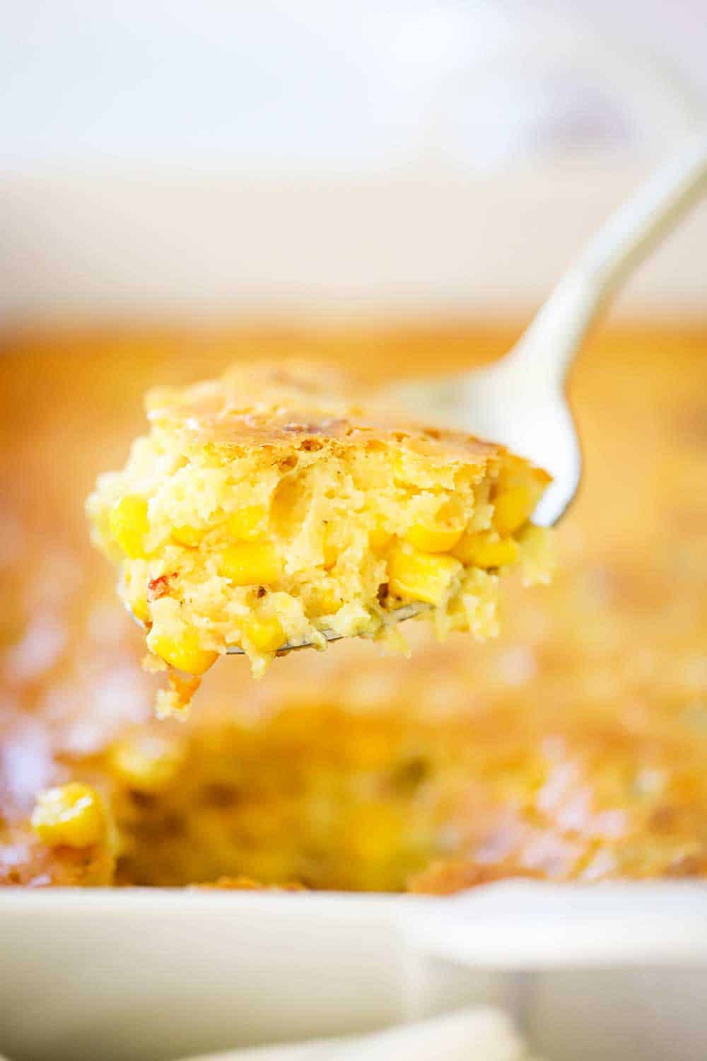 A gold serving spoon holding up a large scoop of corn casserole.