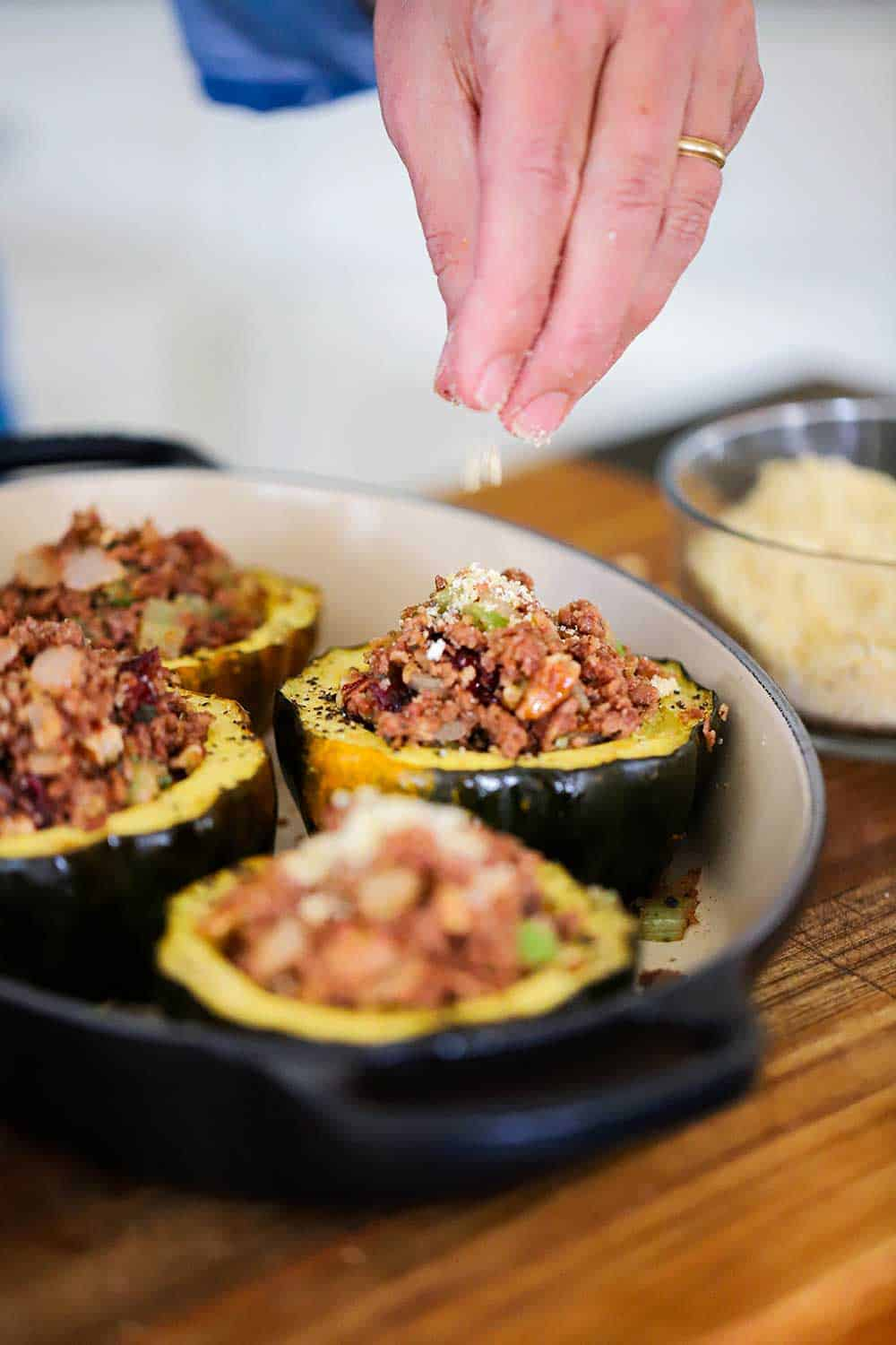 A hand sprinkling bread crumbs onto of stuffed acorn squash in a baking dish.