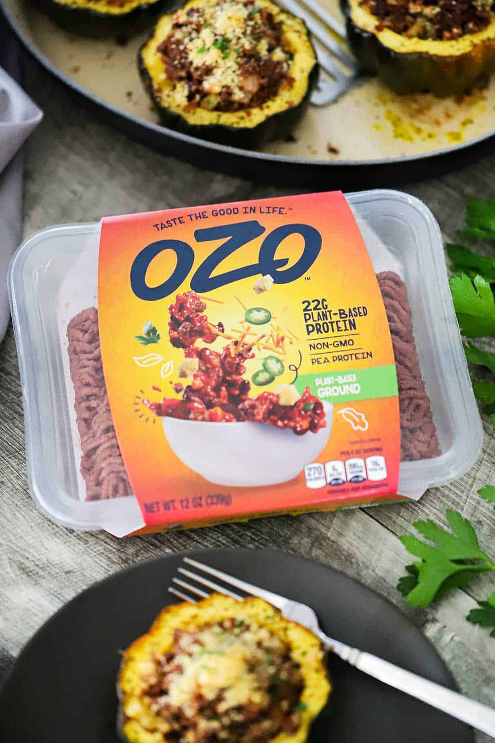 A package of OZO Protein-Based Ground in between a plate and baking dish filled with stuffed acorn squash.