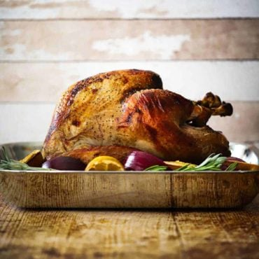 A roasted turkey sitting in a steel roasting pan surrounded by lemons, onions, and herbs.