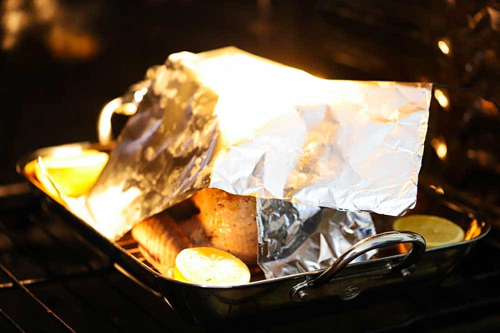 A large piece of foil sitting on top of a turkey in a roasting pan inside an oven.