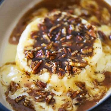 A wheel of baked brie in a baking dish smothered in pecan praline sauce.