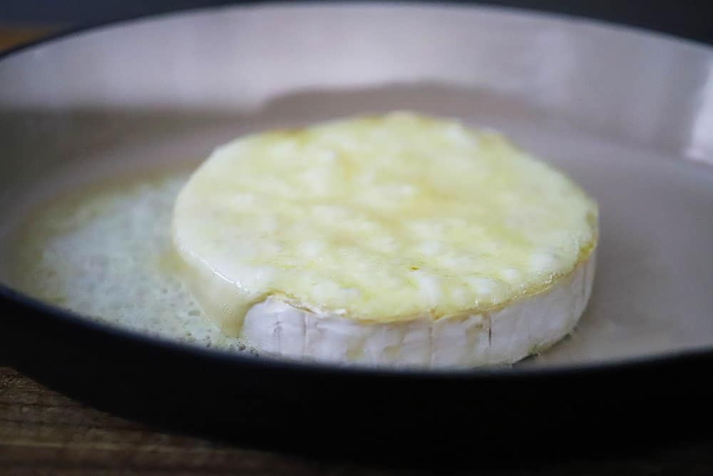 A wheel of brie that has been baked in a baking dish and is bubbling on the surface.