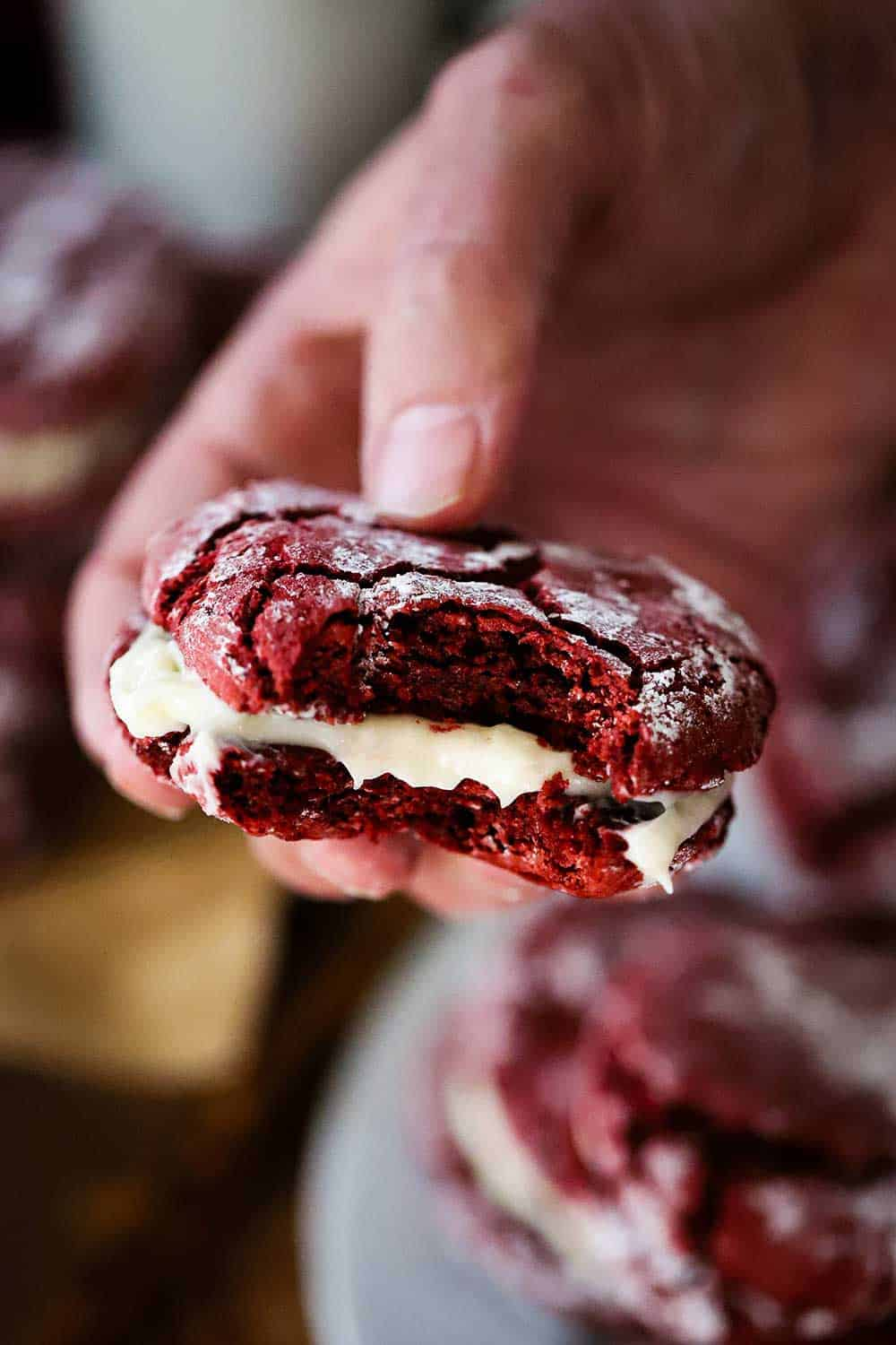 A hand holding a red velvet sandwich cookie with a bite take out of it.