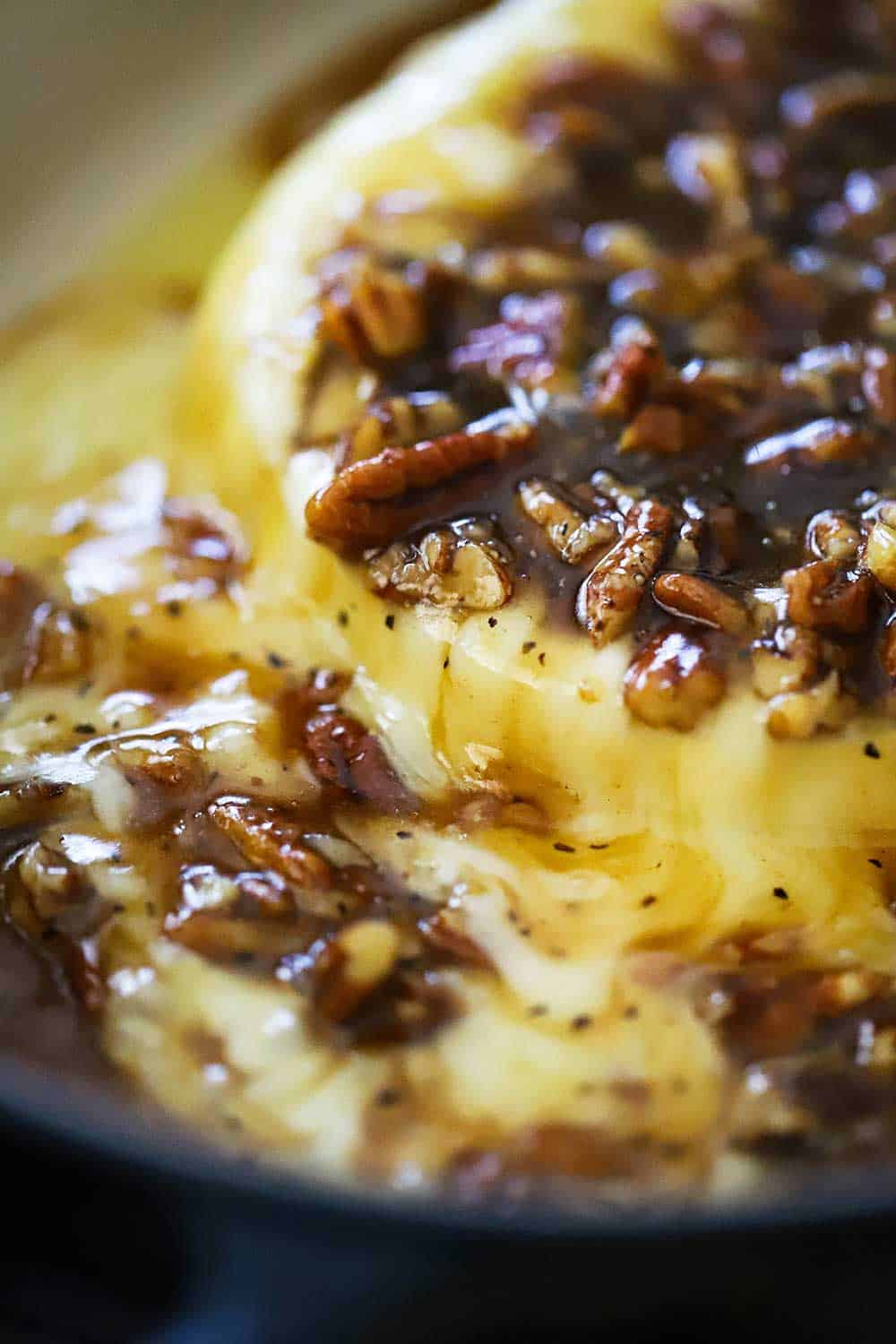 Baked brie with praline sauce in an oval baking dish.