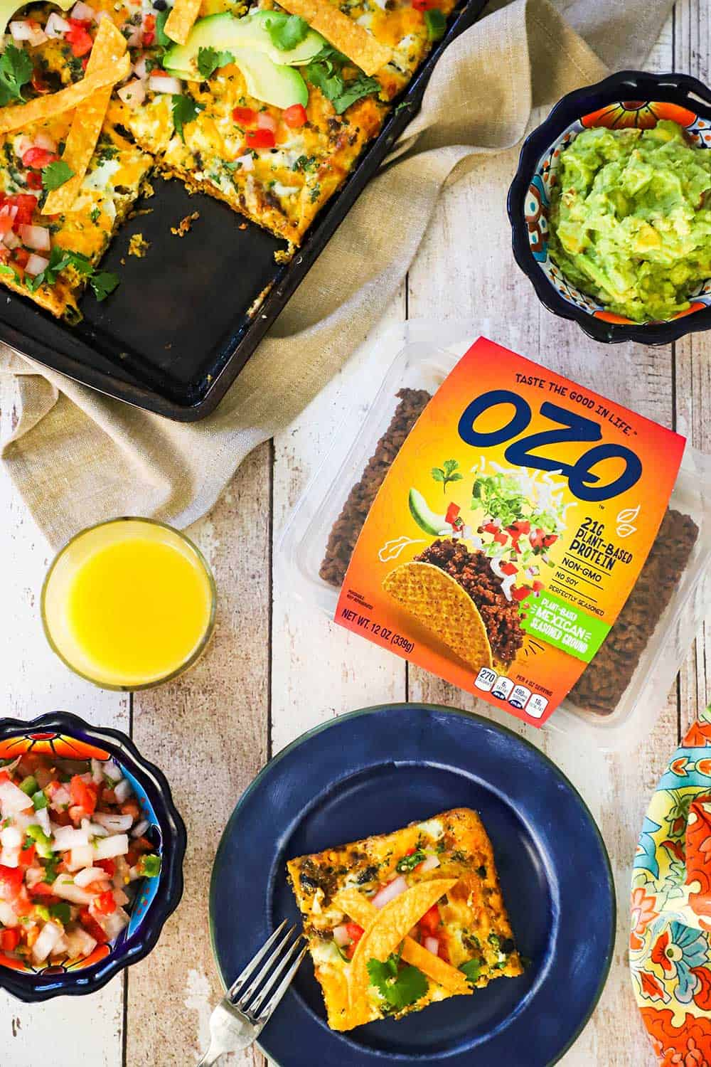 A blue plate with a slice of Mexican frittata on it sitting next to a package of OZO plant-based Mexican ground and a glass of orange juice.