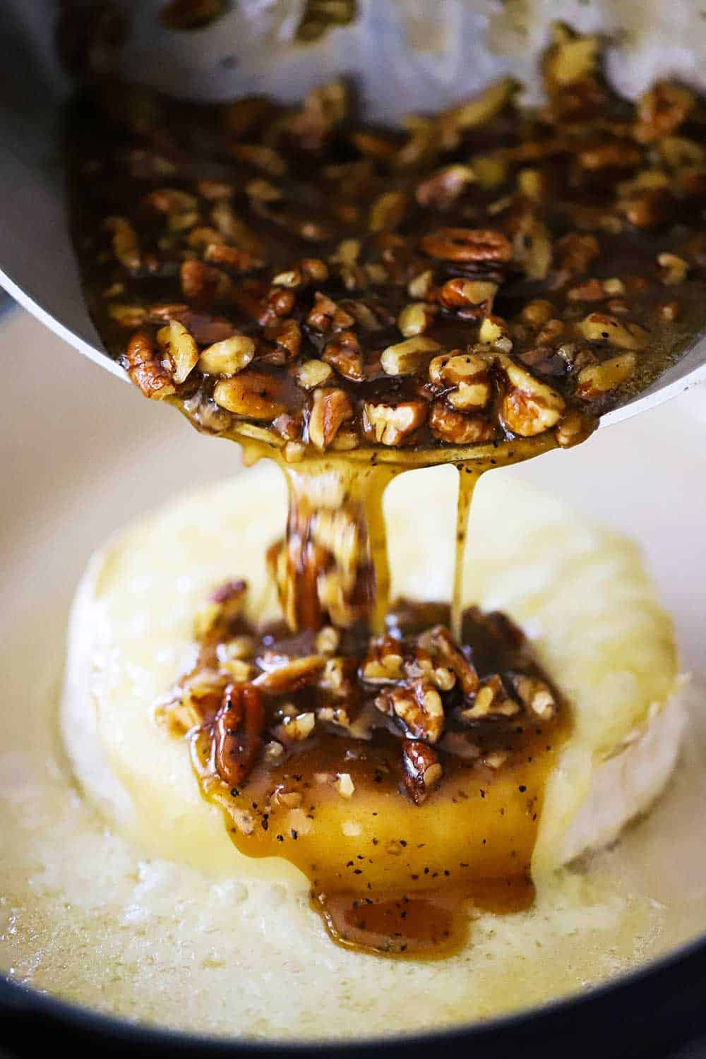 A medium-sized saucepan being used to pour a pecan praline sauce over baked brie.