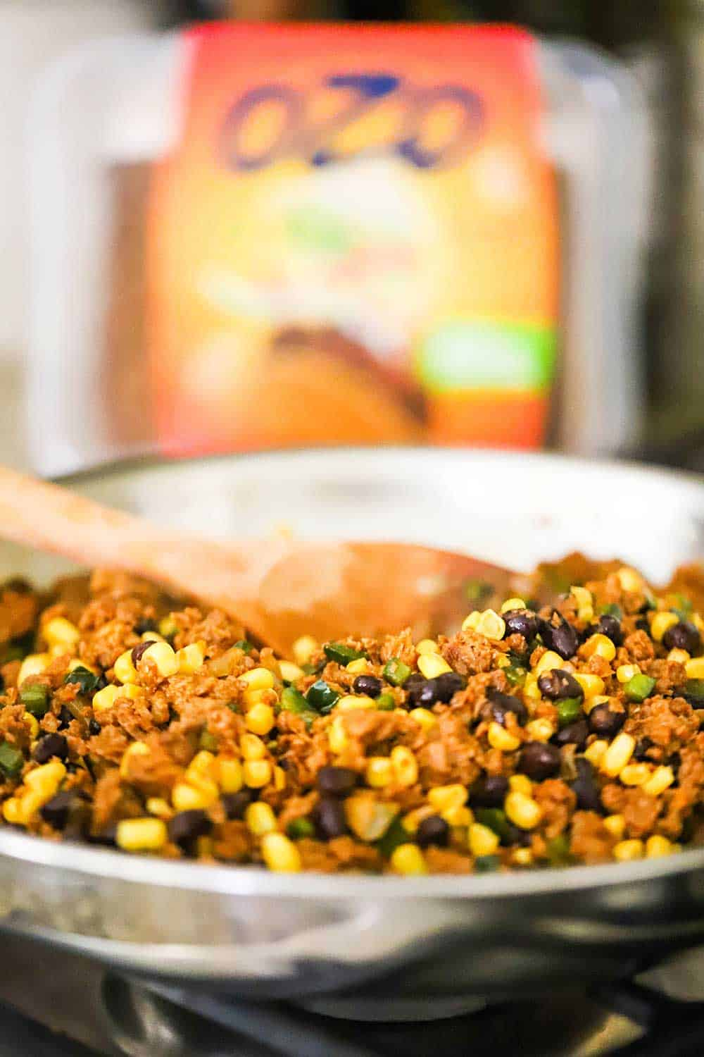 A stainless steel skillet filled with ground plant-based protein and black beans and corn.